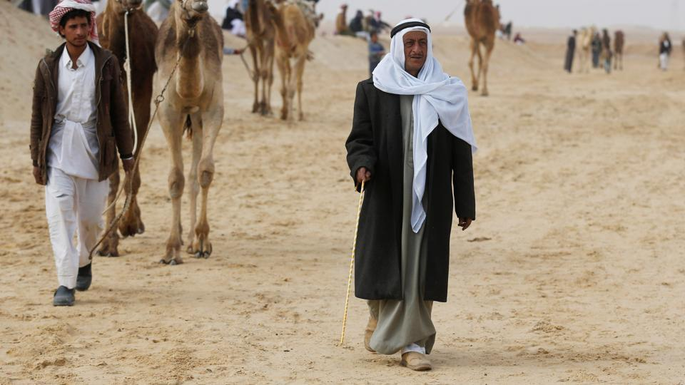 Sheikh Suleiman Abu Shukri walks during the opening of the International Camel Racing festival at the Sarabium desert. (Amr Abdallah Dalsh / Reuters)