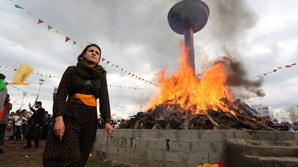 A woman walks past a bonfire during a gathering celebrating Newroz. This weekend, Turkey responded with fury after tens of thousands of people attended a pro-Kurdish protest in Germany, many brandishing Ocalan flags and pro-PKK insignia. But only a few portraits of Ocalan could be seen at the Diyarbakir rally. (Sertac Kayar/REUTERS)