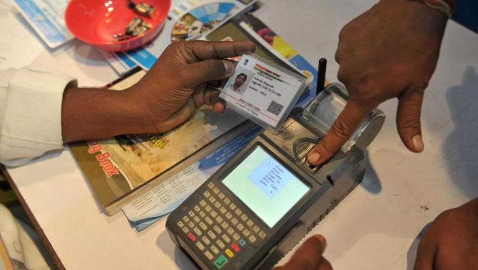 A man gives his thumb impression to withdraw money from his bank account using his Aadhaar card.