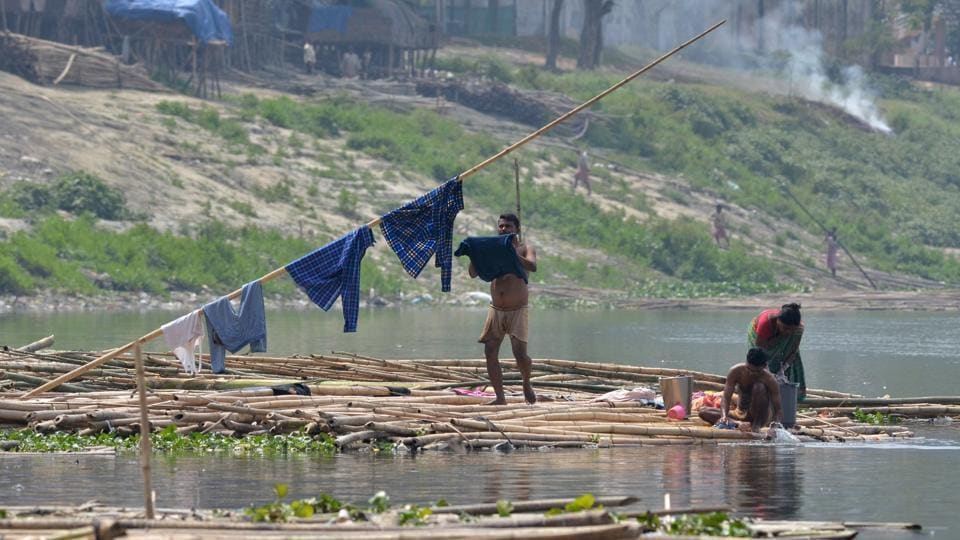 People wash clothes on the banks of the river Brahmaputra in Guwahati on March 21, 2017, on the eve of World Water Day. (Biju BORO / AFP)