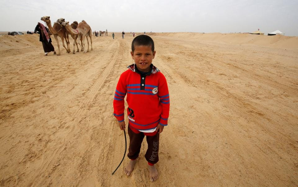Fahad, an 8-year-old jockey, looks on during the opening of the International Camel Racing festival . (Amr Abdallah Dalsh / Reuters)