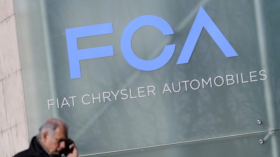 A man walks past the logo of Fiat Chrysler Automobiles (FCA) at the Fiat Mirafiori car plant in Turin, northern Italy.