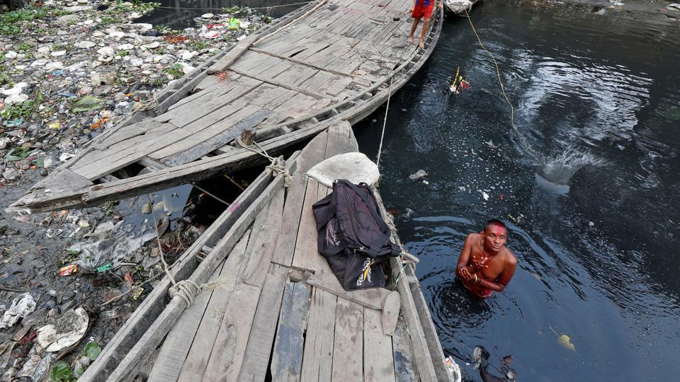 A man offers a prayer as he takes a dip in the polluted waters of Tolly's Nullah in Kolkata. (Rupak De Chowdhuri / REUTERS)