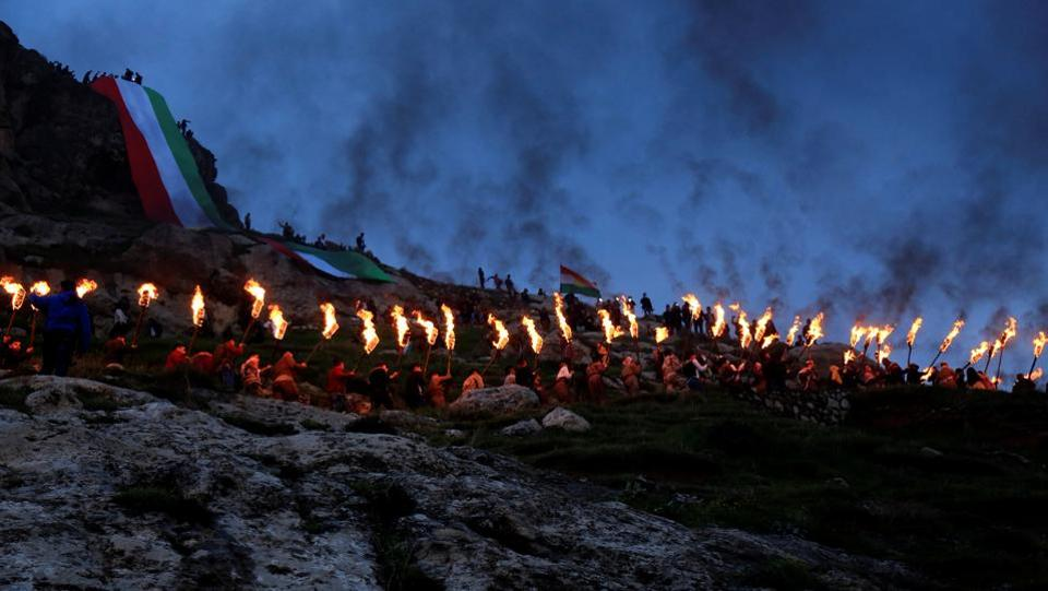 Iraqi Kurdish people carry fire torches up a mountain, as they celebrate Newroz Day, a festival marking their spring and new year, in the town of Akra, Iraq. (Ari Jalal/REUTERS)