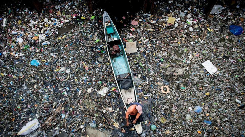 A worker collects garbage from the Marilao River in Bulacan, north of Manila. Pure Earth, formerly known as the Blacksmith Institute, a non-governmental organisation that works to solve pollution problems in the developing world, named Marilao River as one of the 30 dirtiest places in the world in 2007. (Noel CELIS / AFP)