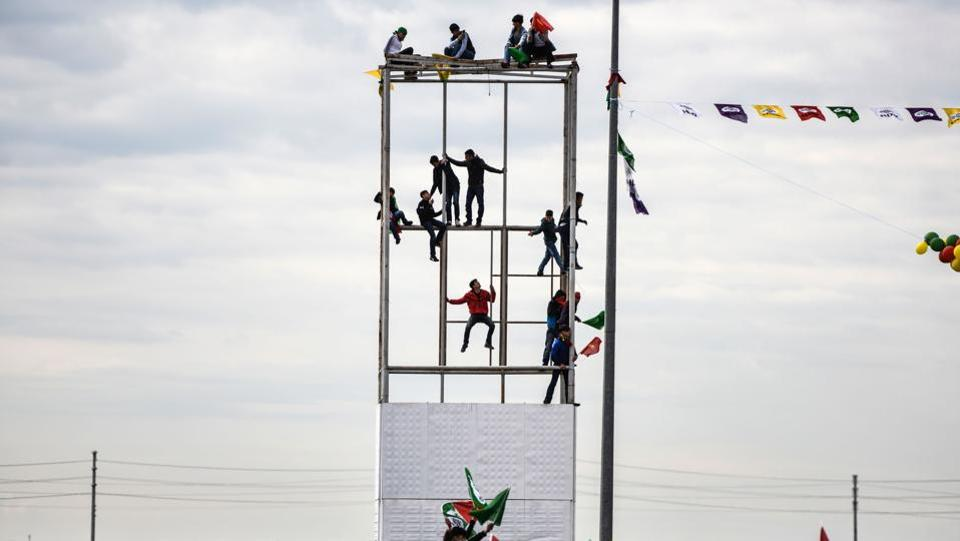 Young men climb on a  during the celebrations.  It was at the Diyarbakir Newroz celebrations in 2015 that the jailed leader of the outlawed Kurdistan Workers' Party (PKK), Abdullah Ocalan, in a statement read by an MP, called for an end to its four-decade armed struggle against the Turkish state. (Bulent Kilic/AFP)