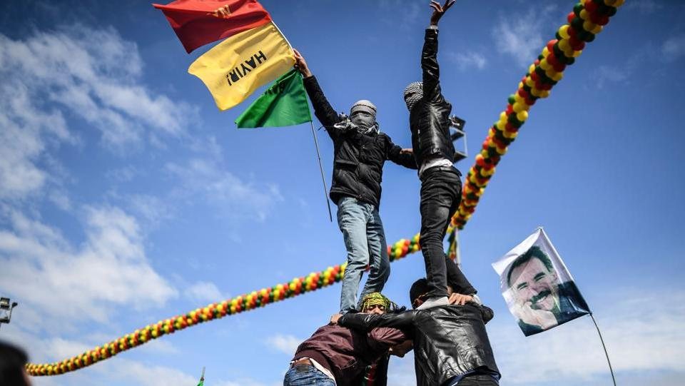 Young men build a human pyramid as Turkish Kurds gather for Newroz celebrations for the new year. Tens of thousands of people celebrated the New Year festival of Newroz in Turkey's overwhelmingly Kurdish city of Diyarbakir on Tuesday, even as police killed a man who claimed to be carrying a bomb. (Bulent Kilic/AFP)
