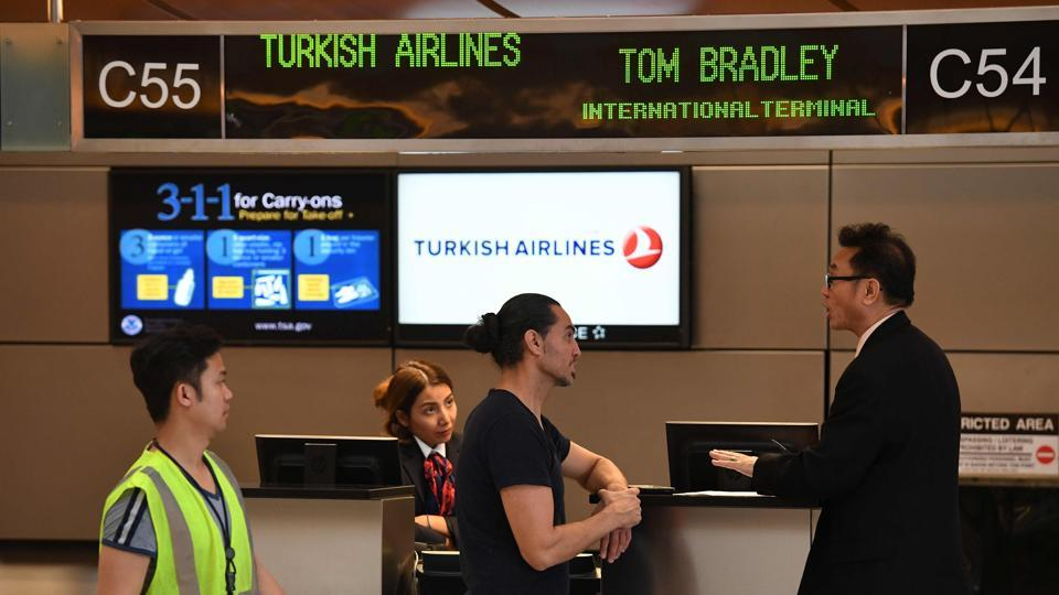 A passenger talks with a Turkish Airlines manager beside a check-in counter at Los Angeles International Airport in Los Angeles, California on March 21, 2017. From toothpaste to pocket knives, ink cartridges and scissors, the US cabin ban on electronic devices on flights from the Middle East and North Africa adds to a long list of products already blacklisted on international flights.