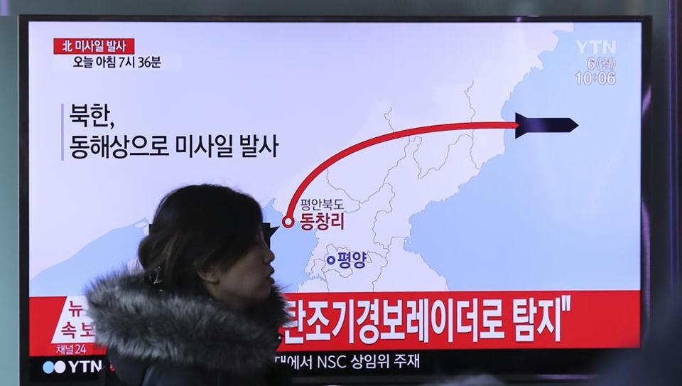 A visitor walks by the TV screen showing a news program reporting about North Korea's missile firing, at Seoul Train Station in Seoul, South Korea.