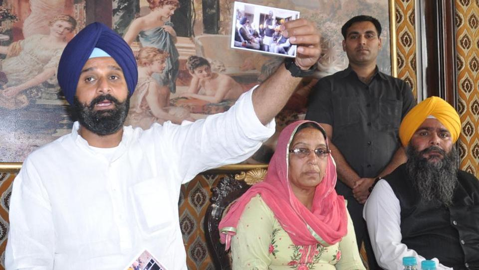 SAD leader Bikram Singh Majithia showing picture of accused Kunnan Singh with Congress leaders in Amritsar on Wednesday.
