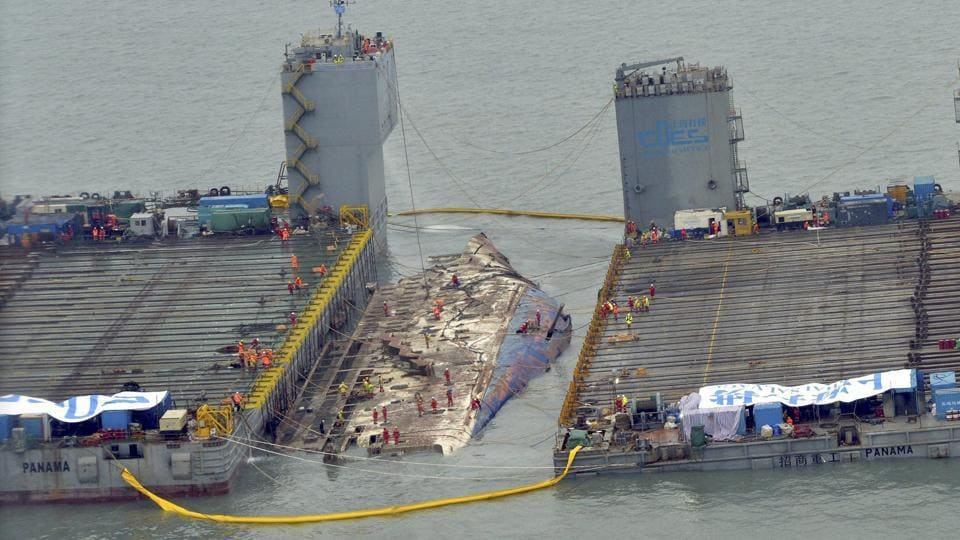 Workers prepare to lift the sunken Sewol ferry (centre) in waters off Jindo in South Korea on Thursday.