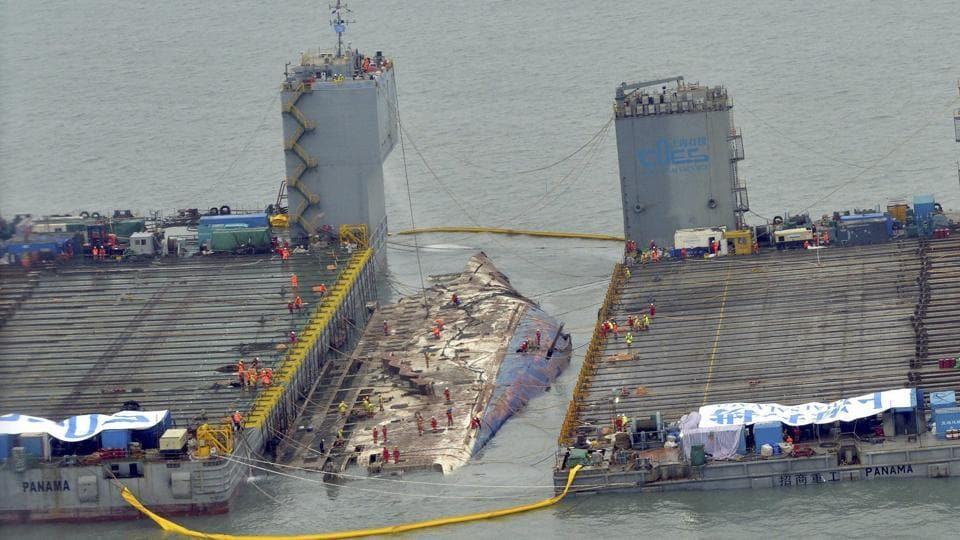 Workers prepare to lift the sunken Sewol ferry in waters off Jindo, South Korea. Several relatives watched the much-anticipated operation unfolding from a boat near the site. (AP/PTI)