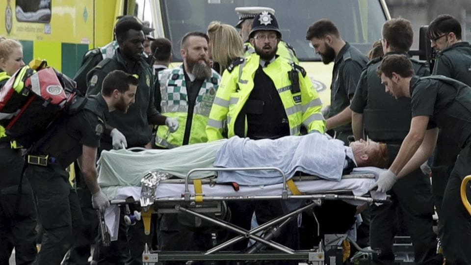 Emergency services staff provide medical attention to injured people on the south side of Westminster Bridge, close to the Houses of Parliament in London.