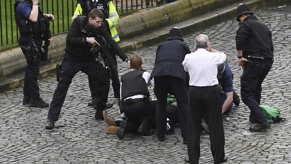 A policeman points a gun at a man on the floor while standing on a knife as emergency services attend the scene outside the Palace of Westminster, London, on March 22, 2017. A man with a knife attacked a police officer at Parliament and was shot by officers.