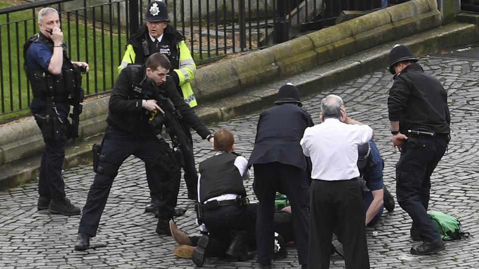 A policeman points a gun at a man on the floor as emergency services attend the scene outside the Palace of Westminster, London, Wednesday, March 22, 2017.  (Stefan Rousseau / AP)