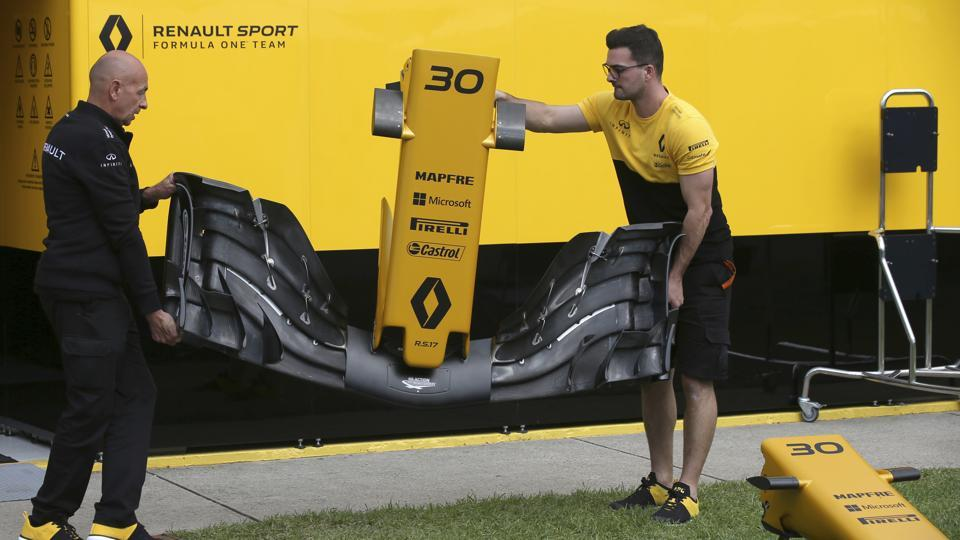 Technicians from Renault Sport carry a nose piece for a car at the track in Melbourne on  Thursday. Sunday's season-opening Australian Grand Prix, where F1 rule changes requiring wider tires, greater aerodynamics thanks to among other things a sophisticated and wider nose, bigger fuel loads and increased downforce are expected to make the heavier cars significantly faster than previous years.  (AP)