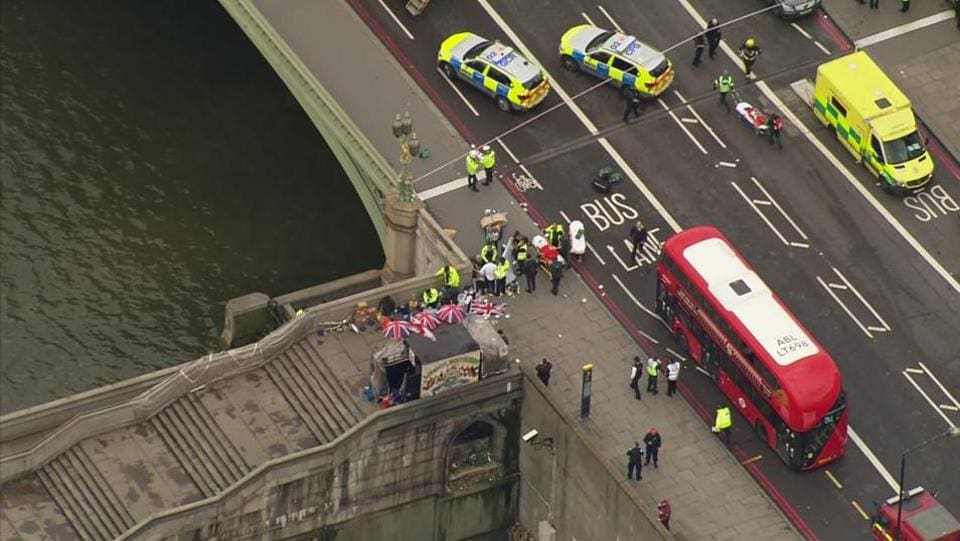 In this image taken from video emergency personnel gather around a body on the southside of Westminster Bridge that leads to the Houses of Parliament in London, Wednesday, March 23, 2017 after the House of Commons sitting was suspended as witnesses reported sounds like gunfire outside.  (ITN via AP)