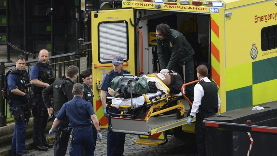 An attacker is treated by emergency services outside the Houses of Parliament in London, Wednesday, March 22, 2017.  (Stefan Rousseau / AP)