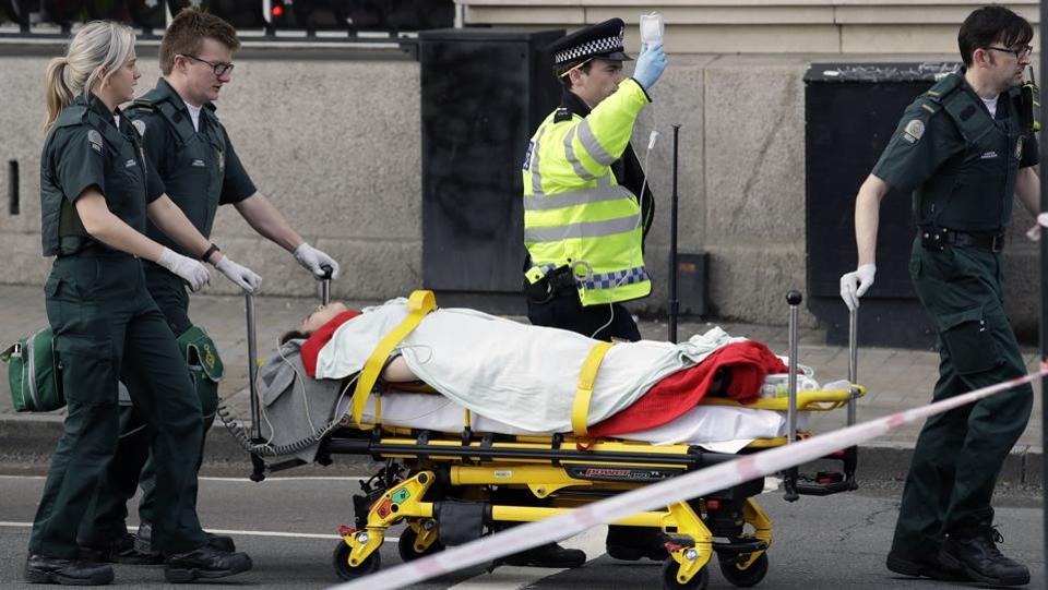 Emergency services transport an injured person to an ambulance, close to the Houses of Parliament in London, Wednesday, March 22, 2017. (Matt Dunham / AP)