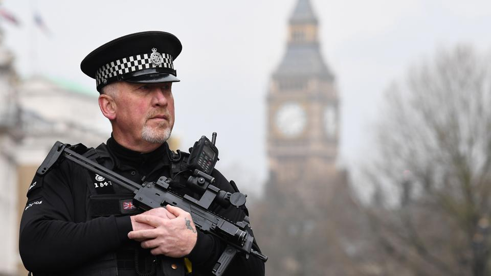 An armed police officer patrols by a security cordon set up along Whitehall by the Houses of Parliament in London.