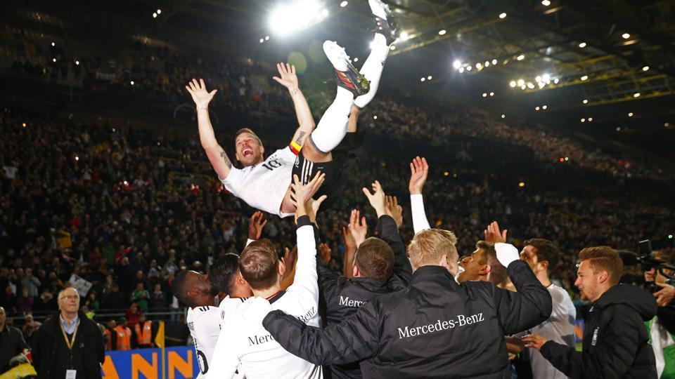 Germany's Lukas Podolski is thrown in the air by teammates after his final appearance for his country in a friendly against England.
