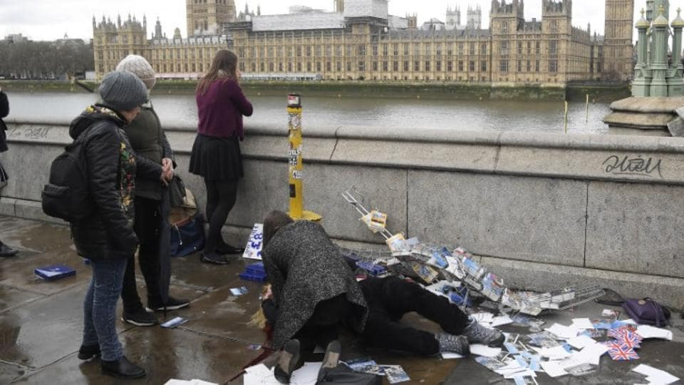 An injured woman is assisted after an attack on Westminster Bridge in London.