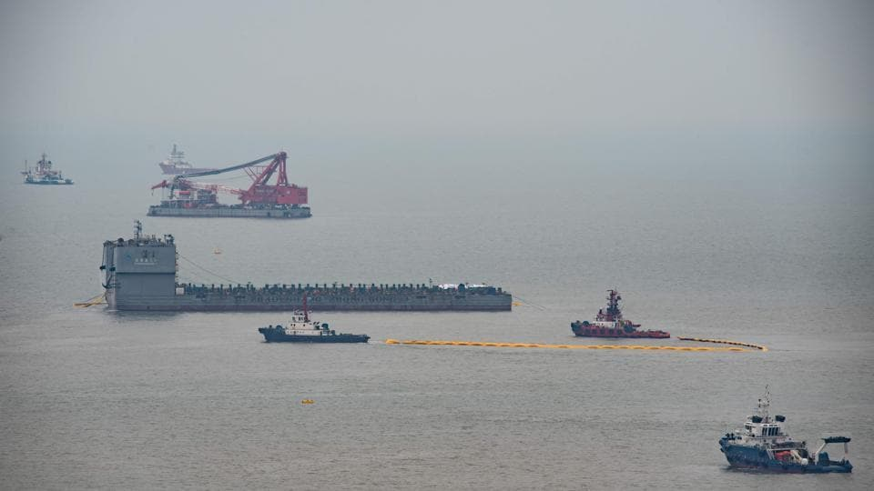 This general view taken from Donggeochado island shows the ongoing salvage operation of the Sewol ferry. Dozens of salvage operators walked over the hull after it came to the surface, television pictures showed.  (Ed Jones/AFP)