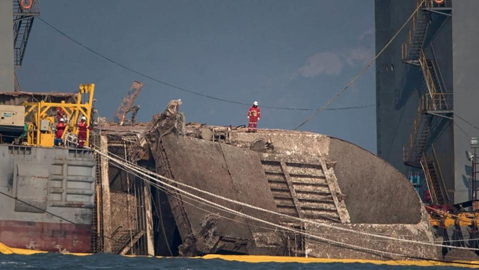 A worker stands on the partially-submerged wreck of the Sewol ferry as it is lifted between two Chinese salvage vessels off the coast of the southern South Korean island of Jindo. Television pictures showed one side of the 140-metre-long vessel, its white structure rusted and filthy, above the waves between two giant salvage barges.  (Ed Jones/AFP)