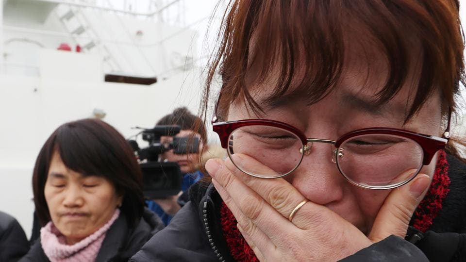 Relatives of the missing from the Sewol ferry disaster cry as they watch as a part of the damaged Sewol ferry being raised.  (AFP)