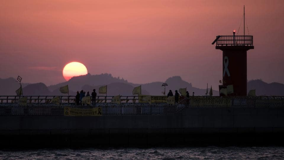 Sun setting behind a pier adorned with tributes to victims of the Sewol ferry disaster at Paengmok harbour on the southern island of Jindo. (Ed Jones/AFP)