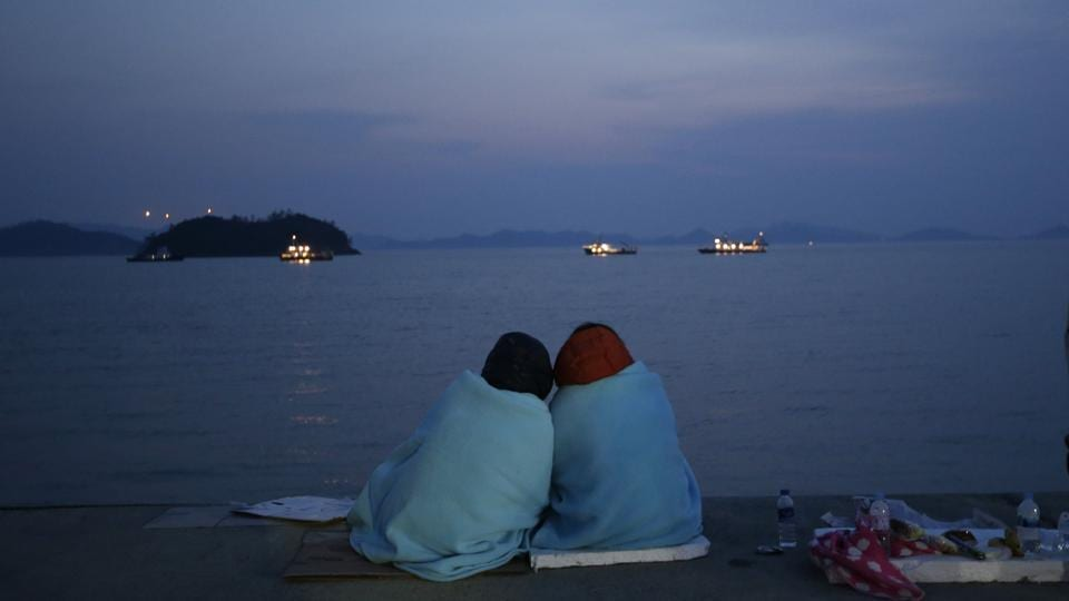 In this April 20, 2014 file photo, relatives of passengers aboard the sunken ferry Sewol sit near the sea at a port in Jindo, South Korea.  Investigations into the disaster, in which 304 people died, concluded it was largely man-made -- the cumulative result of an illegal redesign, an overloaded cargo bay, inexperienced crew and a questionable relationship between the ship operators and state regulators. (Lee Jin-man/AP File Photo)
