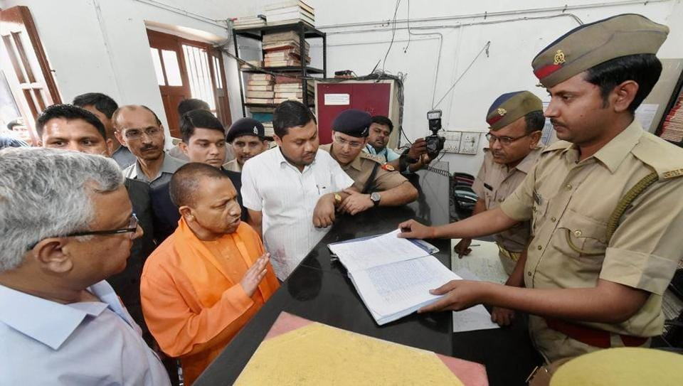 Uttar Pradesh CM Yogi Adityanath speaks with a police personnel during his surprise visit to the Hazratganj police station in Lucknow on Thursday.