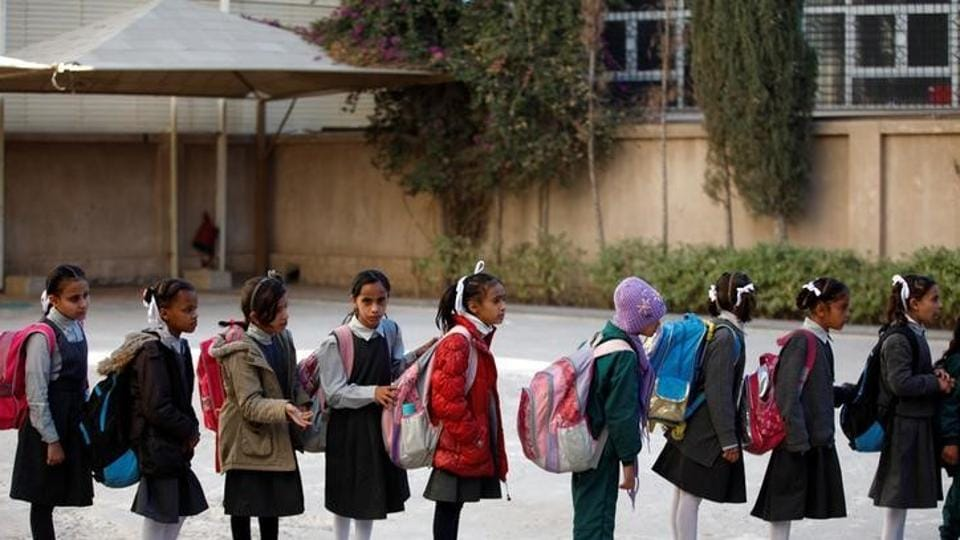Girls stand in line to board a bus to transport them to school from an orphanage. (Khaled Abdullah / Reuters)