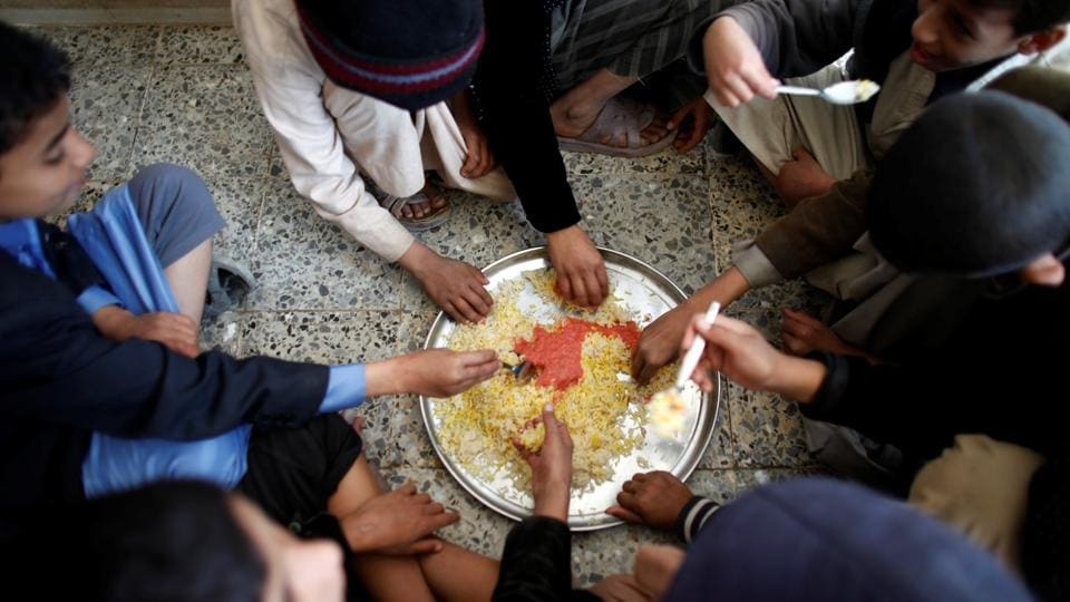 Boys eat rice for lunch at The al-Shawkani Foundation for Orphans Care. (Khaled Abdullah / Reuters)