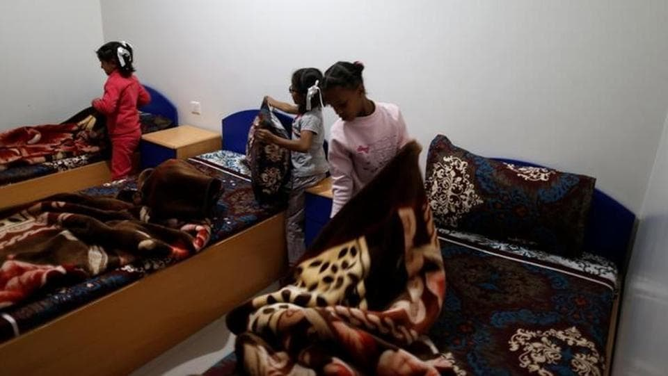 Girls tidy their beds after they woke up at an orphanage in Sanaa. (Khaled Abdullah / Reuters)