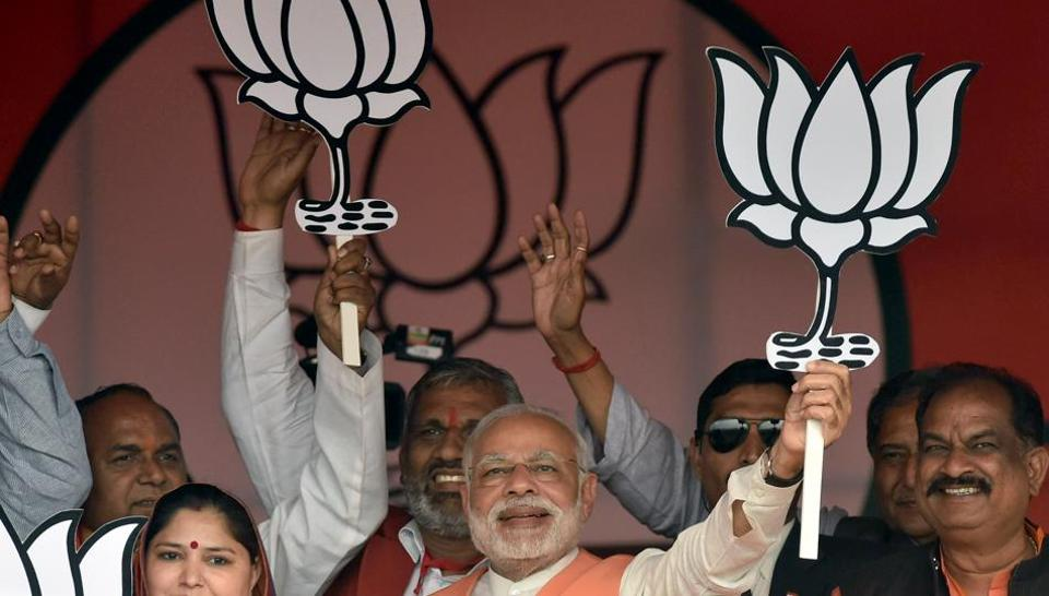 Prime Minister Narendra Modi holds the party symbol during a public rally at Barabanki constituency of Uttar Pradesh.