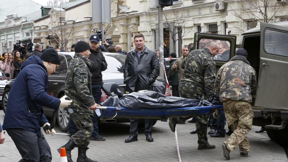 Forensic experts carry the body of Denis Voronenkov, after he was shot dead in Kiev, Ukraine, Thursday, March 23, 2017.