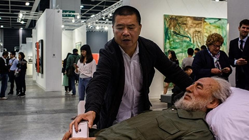 Chinese artist Shen Shaomin places his phone in the hands of a replica of Fidel Castro, part of his 'Summit' project, at Art Basel in Hong Kong.