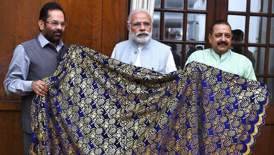 Prime Minister Narendra Modi hands over chaadar to be offered at Ajmer Dargah to Mukhtar Abbas Naqvi and Jitendra Singh in New Delhi.