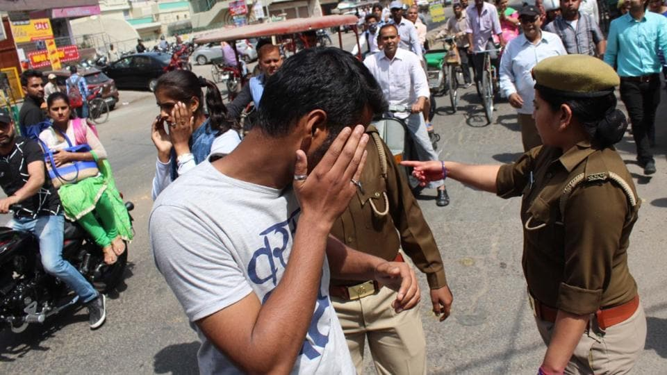 Police question men outside RGPG College for Women in Meerut on Wednesday. Across 11 districts of Uttar Pradesh, cops have hit the streets to carry out a drive against 'Romeos' on the orders of newly sworn-in CM YogiAdityanath.