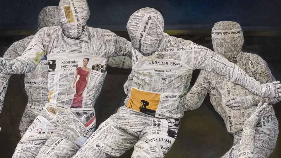 """Indonesian artist Budi Ubrux's striking oil paintings are recognisable by the faceless figures wrapped in newspapers.  The unusual portrayal is a satirical comment on the """"untruthful nature of news coverage""""."""