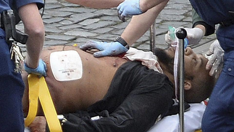 Attacker Khalid Masood is treated by emergency services outside the Houses of Parliament in London.