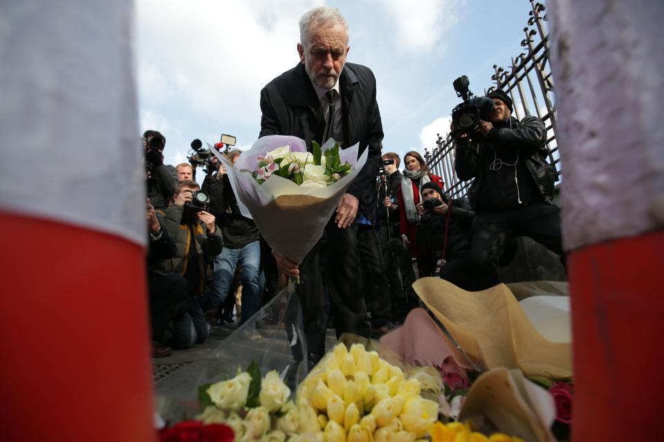 British Opposition Labour Party leader Jeremy Corbyn (C) lays a bunch of flowers at the end of Westminster Bridge by the Houses of Parliament in central London on March 23 after the bridge reopened following the March 22 terror attack.