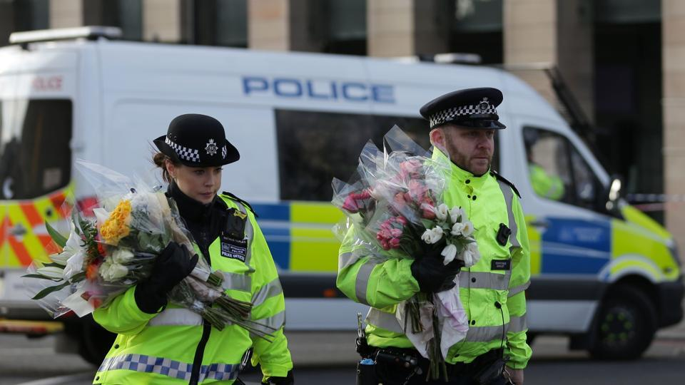 Police officers arrive carrying bunches of flowers to lay in honour of the victims of the March 22 terror attack at the end of Westminster Bridge by the Houses of Parliament in central London on March 23, 2017 after the bridge reopened. Britain's parliament reopened on Thursday with a minute's silence in a gesture of defiance a day after an attacker sowed terror in the heart of Westminster, killing three people before being shot dead.