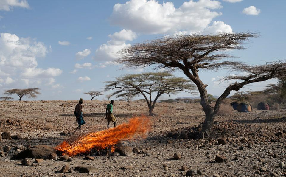 A Turkana tribesman walks in front of burned goats' carcasses in a village near Loiyangalani. (Goran Tomasevic / Reuters)