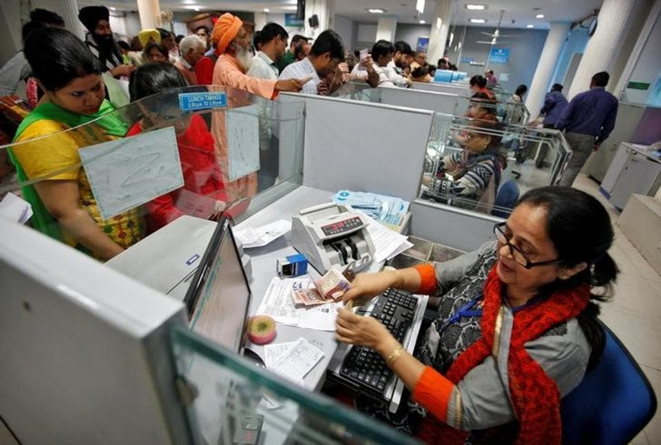 A cashier counts Indian banknotes as customers wait in queues inside a bank