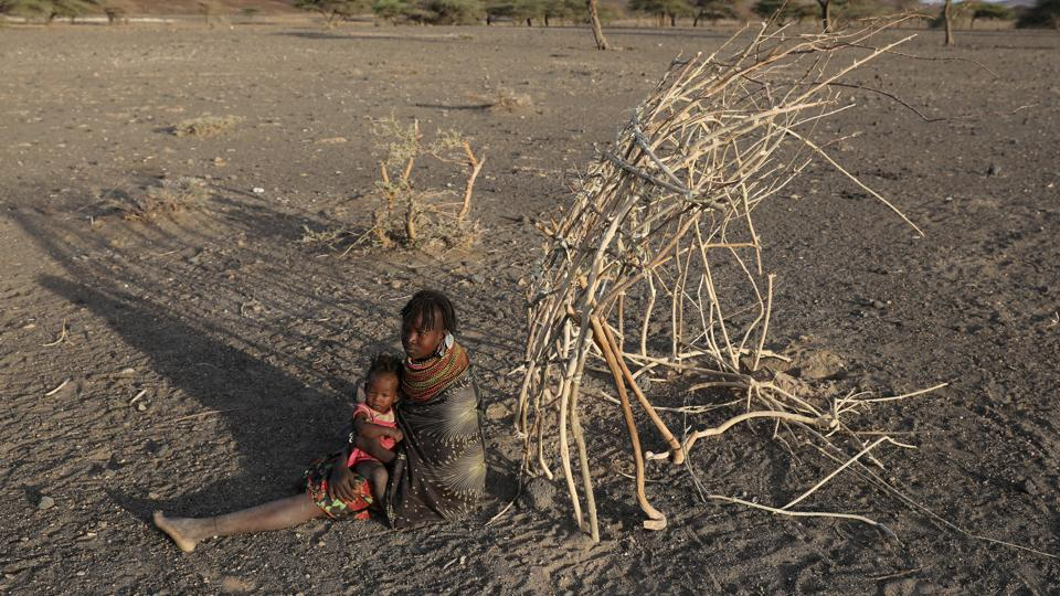 A Turkana tribeswoman holds her child next to the construction site of her cabin in a village near Loiyangalani. (Goran Tomasevic / Reuters)