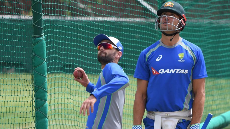 Australia's Nathan Lyon (L) is watched by teammate Ashton Agar as he throws a ball in the nets. (AFP)