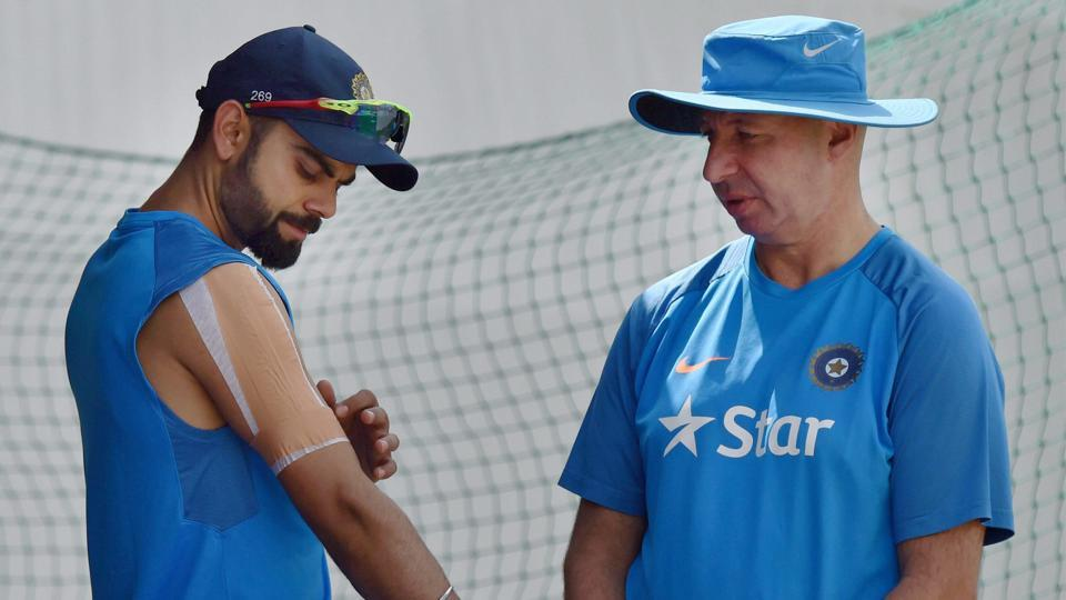 Virat Kohli with team physiotherapist Patrick Farhart during a practice session at HPCA Stadium in Dharamsala ahead of the fourth and deciding Test against Australia.