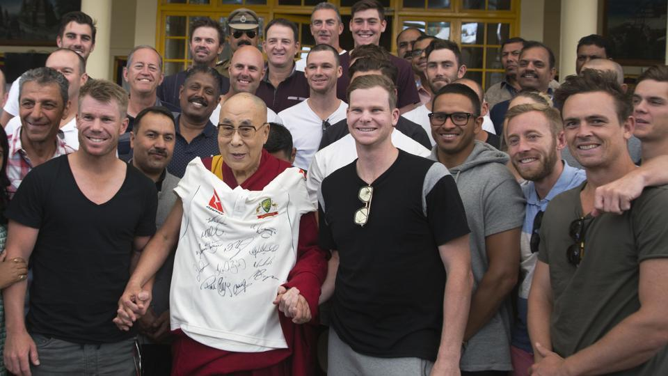 The Dalai Lama slings a t-shirt signed by the Australian cricket team players as he poses for a photograph. (AP)